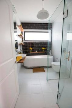 Bathroom from The Block NZ - black glass tiles with white grout, mosaic bath base and recycled timber shelves and vanity.