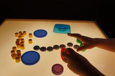 Tekeningen maken met dopjes op de lichtbak. Voorwerpen ten opzichte van elkaar oriënteren in het vlak. Vlakke vormen verkennen.