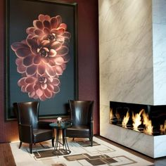 Modern fireplace with wing chairs, great lighting and painting
