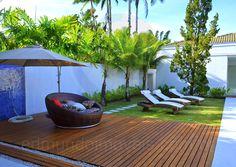 Uma área gramada faz a conexão com a piscina e conta com um deck em madeira e espreguiçadeiras para os banhos de sol.