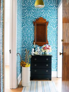 Bright blue damask wallpaper and white moldings add energy to this entryway.