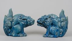 Pair of Japanese ceramic turquoise-colored beasts with ferocious faces, large ears, long hairy tails.