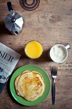 pancakes, orange juice, coffee, newspaper, wooden table