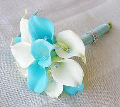 This is a beautiful bouquet made with the most realistic flowers available. So amazing to the touch that people wont be able to tell they are not real! Beautiful Floramatique Turquoise Aruba Blue Calla Lilies mixed with Off White Calla Lilies accented with Crystals in Blue (we also have Clear).  The bouquet measures approximately 7 Wide. Each Calla Lily Measures about 3 Tall x 2 1/4 Wide. The last is a picture of someone holding this size bouquet just for reference.  Please select Aruba Blue…