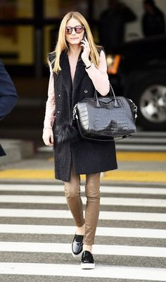 Olivia Palermo wears a light pink sweater, long textured vest, leather skinny pants, platform slip-on sneakers, a Givenchy bag, and mirrored sunglasses