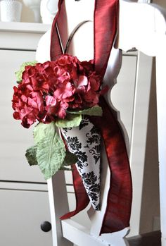 Pew cones hung with ribbon filled with beautiful flowers is a great way to dress up the chapel for your wedding! Red flowers, damask cone color pop