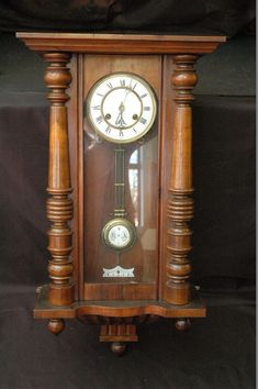 """Early Deutsches Reich Patent German Wall clock, with white porcelain face and set in a wood case with carved columns and reverse finials. CLOCK marked DRP (Deutsches Reich Patent), 62058 N 55006, 368254 DRP. Clock with case measures 31"""" x 15.5"""" x 7"""". Porcelain face with RN lettering. White Porcelain chime placard affixed on bottom. Empire style Brass Pendulum with white porcelain frame and the monogram R A"""