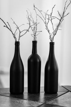 Black painted wine bottles with spray painted twigs. Living room ideas for Halloween. Interior design ideas for Halloween. Halloween decoration.