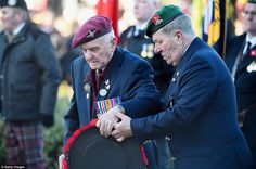 Frail: Two members of Scotland's armed forces help each other handle a wreath as they mark the sacrifices of their colleagues
