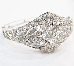 Art Deco hinged diamond bangle in platinum and white gold with stunning hand-done filigree work.