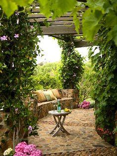 Love the natural stone and the pergola abloom with flowers!  THE spot for birds, bees and butterflies.