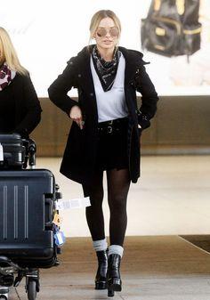 Margot Robbie wears a white t-shirt, parka, miniskirt, bandana, tights, gray socks, and platform boots with aviator sunglasses