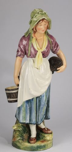Continental majolica figure of a milk maid, late 19th or early 20th century, depicting a standing peasant woman wearing 18th century garb including a pale green bonnet and a striped skirt holding a pail in one hand and having a three legged stool under the other arm, resting on a circular naturalistic base marked with a series of impressed numbers.