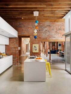 Inspiring industrial style kitchen. The timber, brick and white works a treat especially with the bright pendant lights!