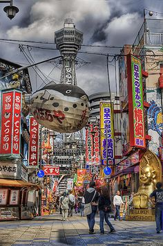 """Tsūtenkaku (通天閣), lit. """"Tower Reaching Heaven"""", owned by Tsūtenkaku Kanko Co., Ltd. is a well-known landmark of Osaka, Japan and advertises Hitachi, Ltd. It is located in the Shinsekai district of Naniwa Ward, Ebisu Higashi 1-18-6. Its total height is 103 m: the main observation deck is at a height of 91 m."""