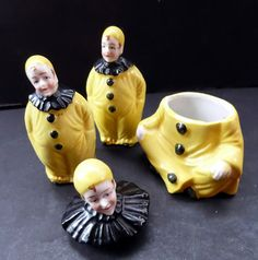 This is a very rare little cruet set which dates to the 1930s.  The set consists of three pieces - a little salt and pepper shaker in the form of a Pierrot - each little figure wears a yellow one-piece costume in bright sunshine yellow with a black ruff and three black buttons on the front. The pierrots wear a little yellow cap. They have original cork stoppers. The cruets on their own are very rare - but exceedingly rare is the matching mustard or relish pot. This matches the salt and…