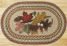Autumn Leaves Braided Jute Placemat, by Capitol Earth Rugs. Features stenciled fall leaves, with braiding in the olive, burgundy, and grey colorway. Artwork designed by Phyllis Stevens. Measures approx 13 x 19 inches. Made of jute, which is a natural fiber, considered to be a sustainable, environmentally friendly material. Water repellent, safe to put near a fireplac...