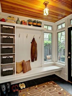entrée moderne aménagée avec un meuble sur mesure doté d'étagères, de boîtes de rangement tressées et patères