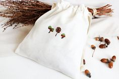 ACORNS HAND EMBROIDERED DRAWSTRING BAG  Delicate hand embroidery pouch with a beautiful acorns embroidery. It is a beautiful pouch made from white thick linen with a rustic look. You can use it as a make up bag, holiday travel bag, home decor bag, you can also use this bag to store vegetables, drie nuts. Store Vegetables, Embroidered Bag, Natural Linen, Holiday Travel, Acorn, Bag Storage, Travel Bag, Hand Embroidery, Delicate