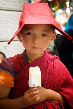 A very young novice Tibetan Buddhist monk eats some ice cream in Yushu