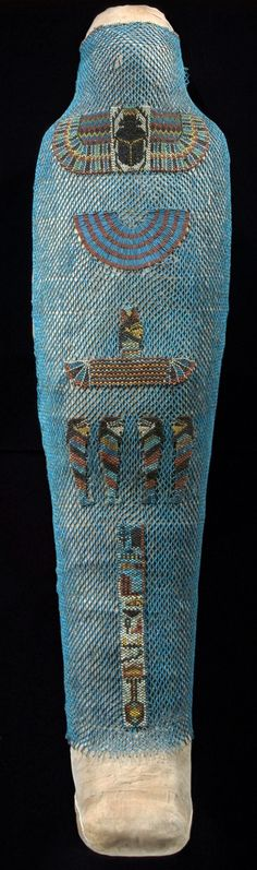 Mummy of Inamonnefnebu (151 x 51.5 cm), Thebes, Egypt, 700–650 BC. A blue faience cylinder bead net covers the underlying shroud. The bead mosaic design consists of a winged scarab on the throat, a collar on the chest with blue and red cylinder beads, a winged goddess on the abdomen, and four Sons of Horus on the thighs. Hieroglyphs on the lower legs say: An offering which the King gives to Osiris, Lord of Aby[dos], may he grant a good burial | Mummy; linen; faience