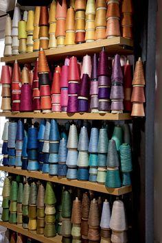 Sur des étagères les bobines de fil coloré utilisées pour les créations textiles Manuel Canovas Coin Couture, Sewing Art, Love Sewing, Yarn Display, Linen Dress Pattern, Fabric Photography, Sewing Room Organization, Leather Workshop, Textiles