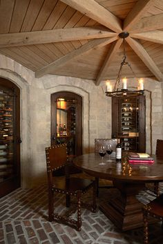This lower-level wine cellar was designed to capture the essence of an old-world Raskellar, with all the amenities of today's technology. From the locally reclaimed brick floor to the carvernous architecture and rustic furnishings, this space feels like a different place & time. The cleverly designed wine storage behind finger-print activated security panels, makes it the ultimate cellar for a connoisseur.