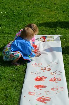 Een hele grote rol papier en lekker spelen met verf en handjes. Buiten in een park.