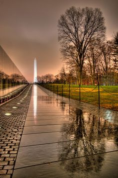 The Memorial Wall, designed by Maya Ying Lin, is made up of two black granite walls 246 feet 9 inches (75 meters) long. The walls are sunk into the ground, with the earth behind them. At the highest tip (the apex where they meet), they are 10.1 feet (3 m) high, and they taper to a height of eight inches (20cm) at their extremities. Granite for the wall came from Bangalore, India and was deliberately chosen because of its reflective quality. Stone cutting and fabrication was done in Barre…