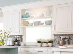 """For extra storage in this kitchen, I used inexpensive wooden stair treads from Lowe's to create open shelving in front of the sunny window,"""" says Sarah."""