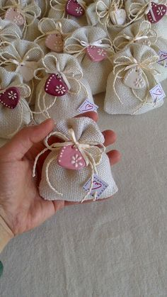 ceramica come mestiere: Sacchetti in iuta con piccoli ciondoli a forma di cuore. Delicate tonalità del rosa con decori in rilievo bianchi.