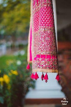 pink gota patti dupatta with pom poms hung on window