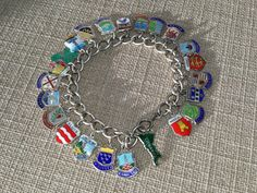 With no less than 23 individual brightly coloured travel shield charms, many of which are stamped silver, hanging from a silver charm