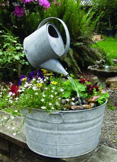 Simple Recycled fountain watering - from certain angles, as if it's hanging in midair over the flowers growing in an old wash tub.