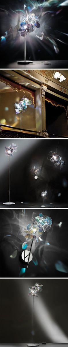 Série de luminaires éditée par Slamp  Le designer Adriano Rachele est à l'origine des ces lampes composées de nombreuses feuilles de polycarbonate irisées que la lumière traverse créant ainsi des superbes effets de reflets. Déclinée en lampe à poser, en lampadaire, en applique et en suspension, Mille Bolle est une véritable sculpture, qui une fois allumée, nous emmène dans un monde onirique.