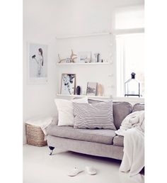 light grey sofa / oversized pillows / white walls and shelves / white floors