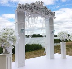 All white wedding altar. White colum arch with bead curtain and white floral arrangements