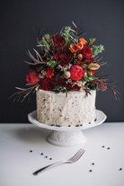 A single-tiered wedding cake topped with lush fall-hued flowers.