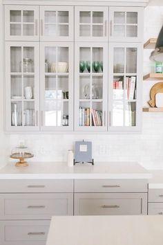 Stunning kitchen features glass front upper cabinets and light gray lower cabinets painted Benjamin Moore Mindful Gray paired with Caesarstone Organic White countertops and a white marble subway tile backsplash.