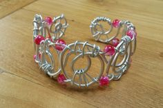Deze opvallende armband is gemaakt van aluminiumdraad met rose kralen.