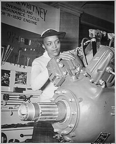 """Inspecting a Grumman Wildcat engine on display at the U.S. Naval Training School (WR) Bronx, NY, where she is a `boot' is WAVE Apprentice Seaman Frances Bates."" (NAID 520638)"