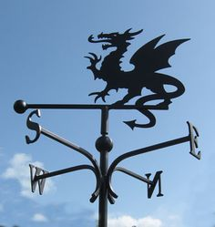 A wide selection of weather vanes and wind sculptures for domestic and public locations Weather Vain, Cottages In Wales, Dragons, Welsh Dragon, Wind Sculptures, Iron Work, Black Dragon, Mythical Creatures, Yard Art