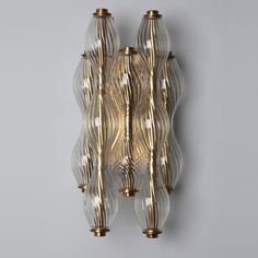 And Objects Wherwell Wall Light- Sconce channelling the luxe look of the 1920s. The Wherwell Wall Light is crafted from hand-blown twisted glass suspended from a traditional polished brass mount.