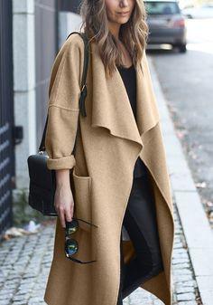 Girl in camel draped open-front long coat, black tee and dark denims