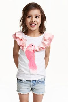 Top with appliqués : Top in slub jersey with sequined embroidery and appliqués on the front and short, doubled frilled sleeves.