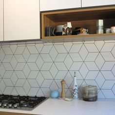 Beautiful geometric tiled splashback, white kitchen, timber accents Tiles available @TILE junket #geelongwest #interiordesign #conceptconsult #tiles #showroom