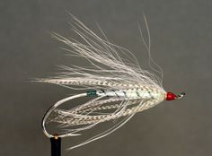 Winter Wonderland - Oak Orchard Flies  -   Hook: Up eye salmon Tip: Oval green tinsel or green wire. Rib: Oval green tinsel or green wire. Body: back half flat silver tinsel, front half white dubing. Body Hackle: White schlappen over the front half of the body. Hackle: Mallard. Wing: White polar bear or substitute. Head: red