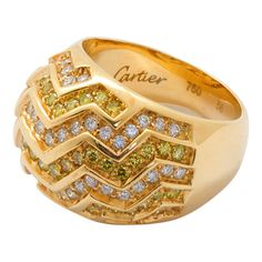 Fancy yellow and white round brilliant cut diamonds in a zig-zag pattern channel set in 18 karat yellow gold dome ring by Cartier. No. 3686