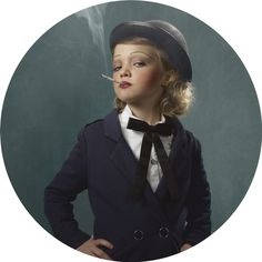 """In her disturbing new series at VII Gallery in Brooklyn, Belgian photographer Frieke Janssens asks viewers if the nostalgia often associated with cigarettes would look as enticing on a much younger crowd. For """"Smoking Kids,"""" Janssens dressed four to nine year olds in period costumes referencing the golden age of cigarette culture. The final touch to their retro-chic ensembles was a glowing cigarette (although Janssens' are made of cheese, candles and incense instead of tobacco)."""