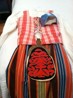 """Swedish Folk Costume from Medelpad Province in central Sweden. Includes white linen blouse w pink embroidery on collar and sleeve, bodice in checkered white and rose with front lacing and linen lining, and wool skirt in multi-colored stripes, The outfit also include a light blue hat with inside lace and folk decorated purse with metal latch. Measurements are skirt waist 30""""; skirt length 33""""; bodice bust 34' and length 20"""" from shoulder down; blouse bust 34"""" & length of 25"""" from shoulder…"""